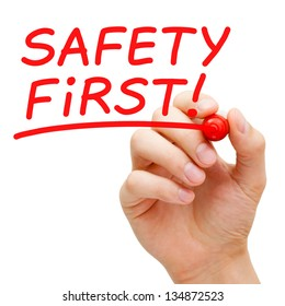 Hand writing Safety First with red marker on transparent wipe board.