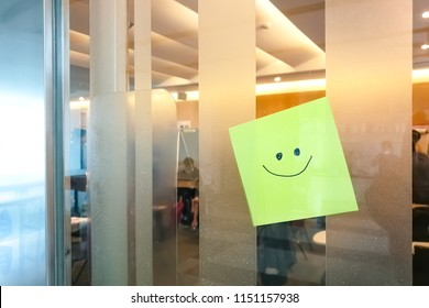 Hand writing of smiling face on yellow post note stick on glass meeting room door