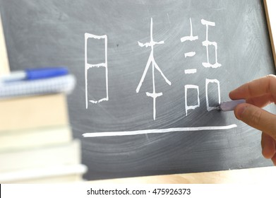 "Hand writing some the word ""Japanese"" in Kana syllabary on a blackboard in a Japanese class. Some books and school materials."