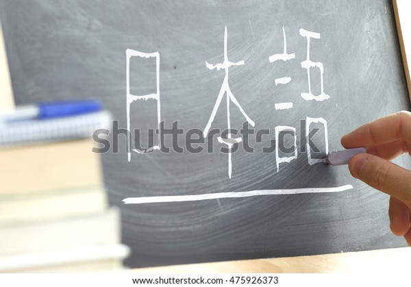"""Hand writing some the word """"Japanese"""" in Kana syllabary on a blackboard in a Japanese class. Some books and school materials."""