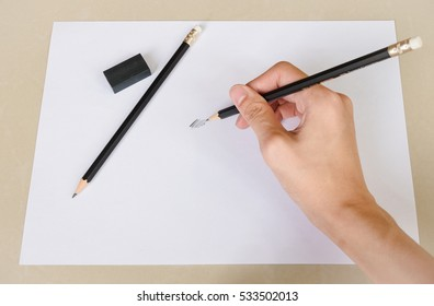 hand writing something by pencil in white paper and eraser rubber on Desk