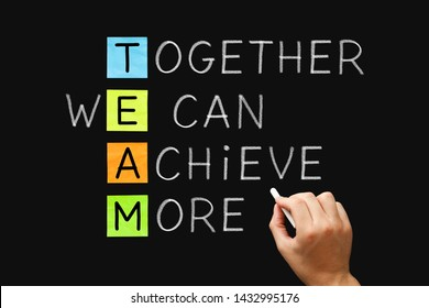Hand writing TEAM Together We Can Achieve More with white chalk on blackboard. Teamwork, synergy or cooperation business concept.