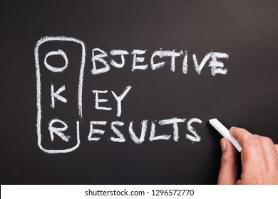 Hand writing text and acronym of OKR (Objective Key Results) on chalkboard