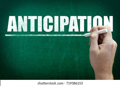 Hand writing the text ANTICIPATION on the blackboard