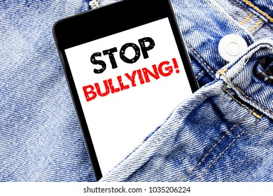Hand writing text caption inspiration showing Stop Bullying. Business concept for Prevention Problem Bully Written phone mobile phone, cellphone placed in man front jeans pocket.