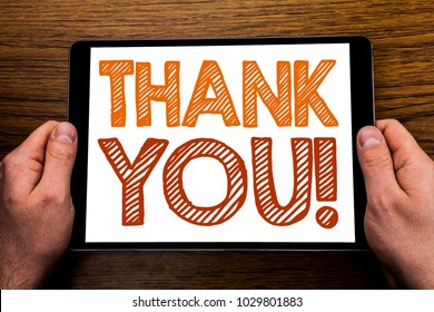 Hand writing text caption Thank You. Business concept for Thanks Message Written on tablet laptop, wooden background with businessman hand, finger holding PC.