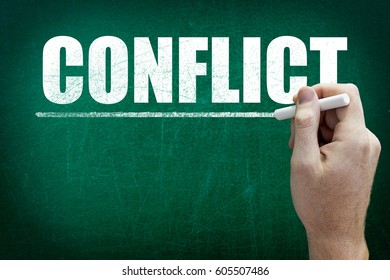 Hand writing the text CONFLICT on the blackboard
