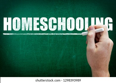 Hand writing the text HOMESCHOOLING on the blackboard