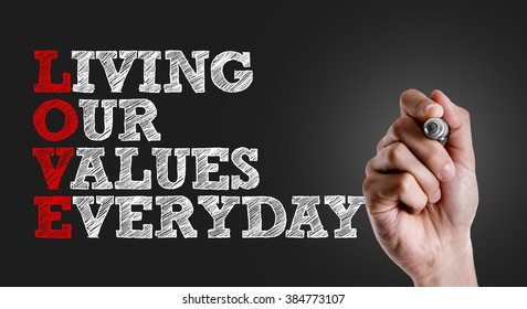 Hand writing the text: Living Our Values Everyday