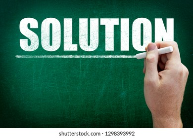 Hand writing the text SOLUTION on the blackboard