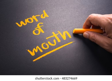 Hand writing text Word of Mouth on chalkboard