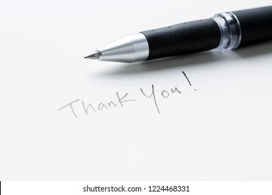 Hand writing thank you note on a piece of white paper