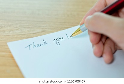 Hand writing thank you on white paper.