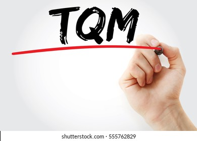 Hand writing TQM - Total Quality Management with marker, concept background