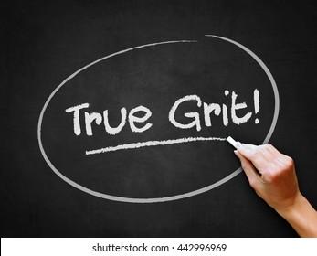 A hand writing 'True Grit!' on chalkboard.