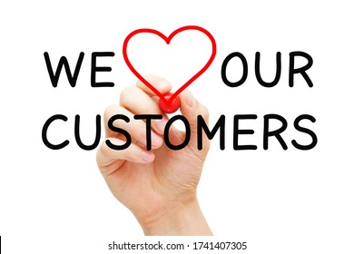 Hand writing We Love Our Customers with marker on transparent wipe board. Customer satisfaction, appreciation and kindness concept.