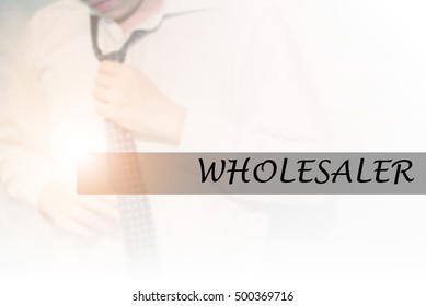 Hand writing WHOLESALER with the young business man on background. Business concept. Stock Photo.