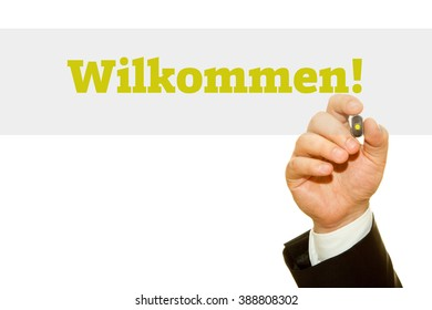 Hand writing Wilkommen! on a transparent wipe board. Welcome message in German language.