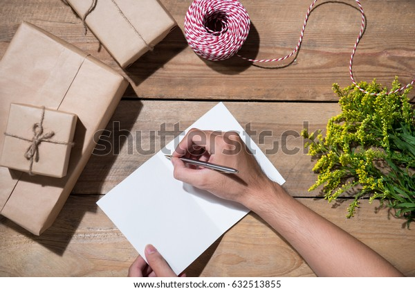 Hand writing wishing with birthday gift on wooden background. View from the top
