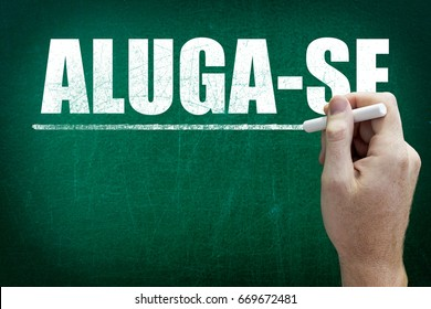 Hand writing the word ALUGA-SE on the blackboard ( For Rent in Portuguese language )