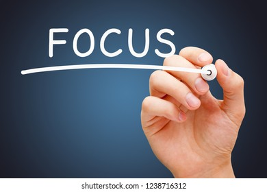 Hand writing the word Focus with white marker on transparent glass board on dark blue background.