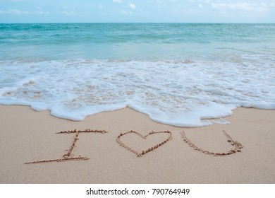 The hand writing word I love you on the beach by the sea with white waves and blue sky background