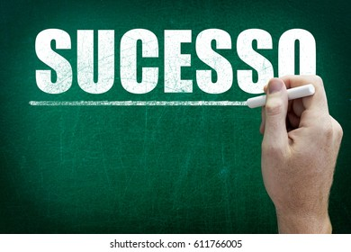 Hand writing the word SUCESSO on the blackboard ( Success in Portuguese language )