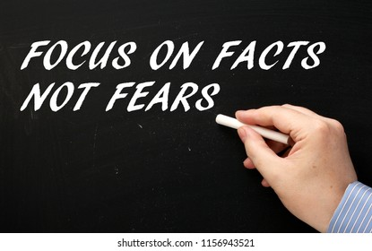 Hand writing the words Focus on Facts Not Fears on a blackboard in white text as a motivational message