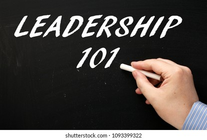 Hand writing the words Leadership 101 on a blackboard as an introduction to the subject of being a leader in business