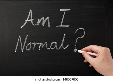 Hand writing the words Am I Normal on a blackboard. A question people ask themselves in times of anxiety,confusion and self doubt which can lead to therapy and a new self awareness.
