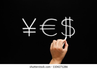 Hand writing YES with yen euro and dollar signs with white chalk on blackboard.