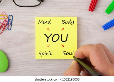 Hand writing You, Body, Mind, Soul and Spirit on note with marker pen and glasses on wooden desk.  Business concept words.Top view.