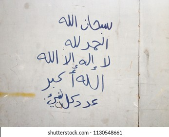 """Hand writings on dirty steel wall, by Arabic language, its mean """"""""God is perfect"""", """"thank God"""", """"There is no god but Allah"""" and """"Allah is Great""""."""