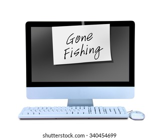 A hand written Gone Fishing sign note is taped to a computer monitor showing that the business man or business woman worker is out on vacation or gone for the day and not working.