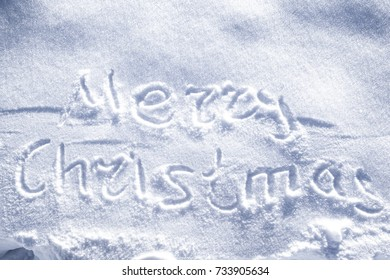 "Hand written ""Merry Christmas""   and christmas tree drawing on snow"