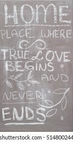 hand written phrase â??home - place whete true love begins and never enasâ?� on dark wooden chalkboard