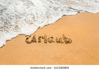 Hand written text in German Urlaub (English translation holidays) on the golden beach sand with coming wave. Concept of summer holidays and vacations at the sea or ocean. Travel and relaxation. - Shutterstock ID 1613383804