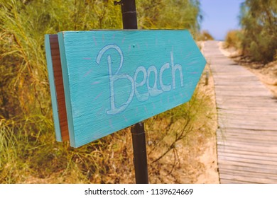 hand written wooden blue, turquoise sign on a metal pole  pointing to the beach which is reached along a wooden path walkway