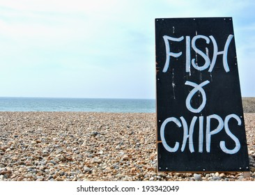 Hand written wooden sign advertising fish and chips on a uk pebble beach.