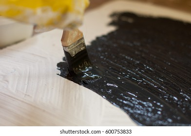hand in yellow glove paints a black surface with white stone. Copy Space.