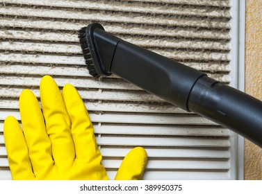 Hand in yellow glove and vacuum cleaner pipe. Ventilation grill cleaning.