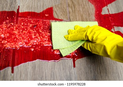 Hand in yellow gloves cleaning red liquid from the parquet floor.Close up on disgusting horror fake brain or puke