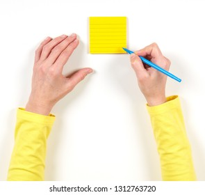 Hand and yellow paper on the table on white background