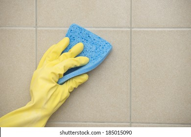 Hand in yellow rubber glove cleaning tiles with blue sponge, copy space.