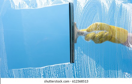 Hand in yellow rubber glove cleaning window on a blue sky