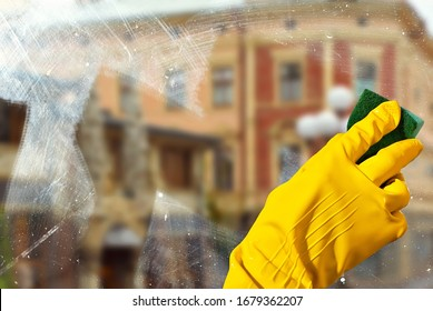 Hand in yellow rubber glove close up. The cleaner washes the window with a sponge. Dirty dusty glass in sharpness.   The architecture is blurred in the background.