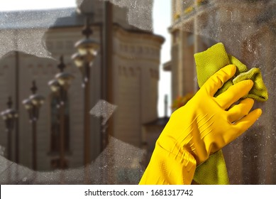 Hand in yellow rubber glove close up. The cleaner washes the window with. Dirty dusty glass in sharpness. City street and buildings outside the window. The architecture is blurred in the background.
