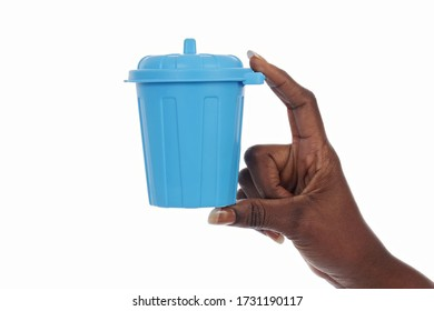 hand young african black woman holding a mini trash bin symbolizing waste reduction on white isolated studio background