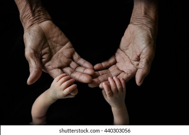 Hand of a young baby touching old hand of the elderly, New family and baby protection from mom concept