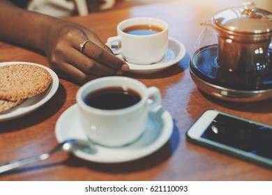 Hand of young black girl touching cup with delicious tea on table with sesame biscuits, teapot, one more cup and smartphone, biracial teenager arm holding white saucer while meeting during breakfast